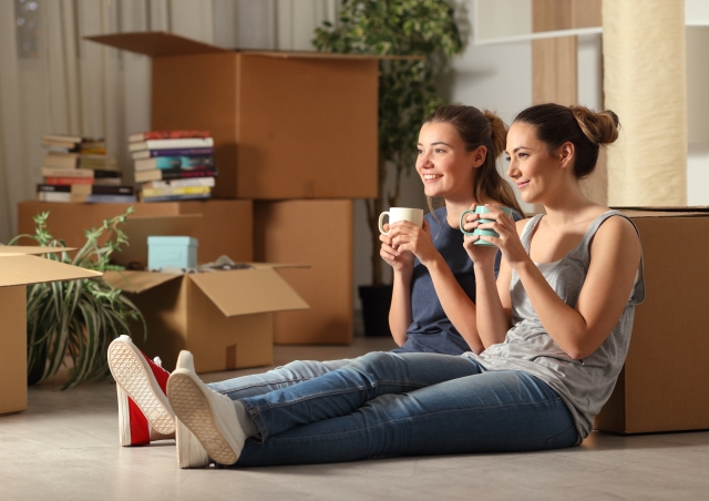 Two girls sitting by boxes